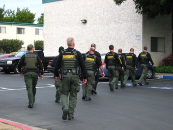 Members of the sheriff's Border Crime Suppression Team walk into an apartment complex in Santee to conduct a compliance search on a probationer.