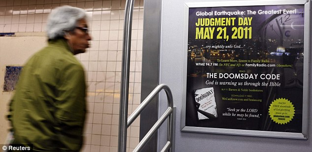Underground movement: A commuter on the New York subway stop at Times Square reads an advertisement for the apocalypse by Family Radio