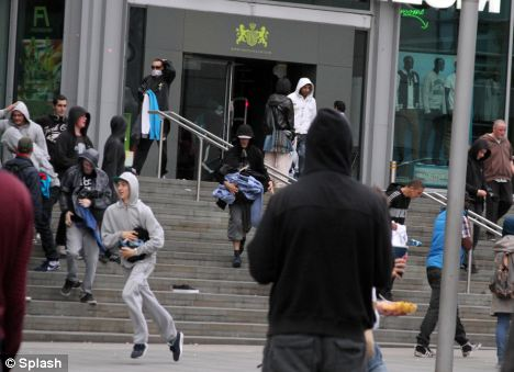 Manchester: Hooded looters laden with clothes run from a Manchester shopping centre