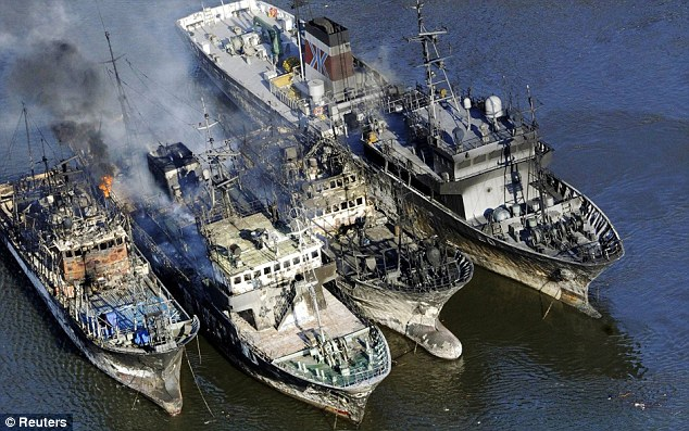 Gutted: Smoke billows from vessels off the harbour in Kesennuma