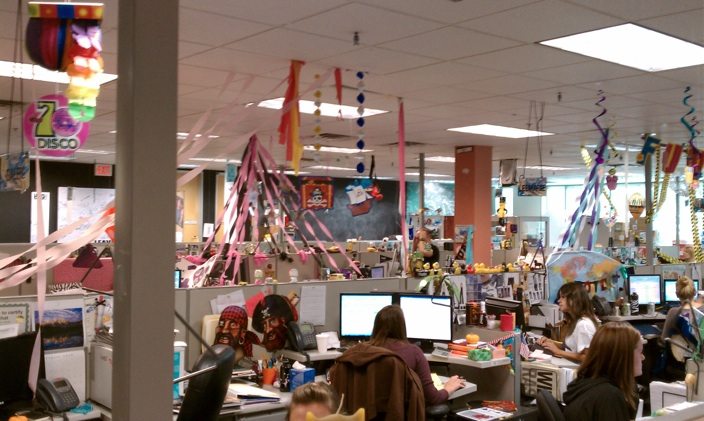 An expanse of desks, with tons of ribbons hanging from the ceiling. Messy but fun.